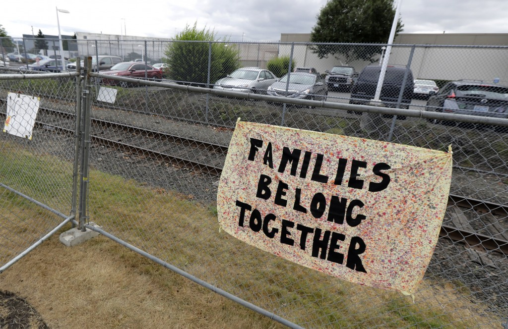 "FILE - This July 10, 2018 file photo shows a sign that reads ""Families Belong Together"" on a fence outside the Northwest Detention Center in Tacoma, W..."