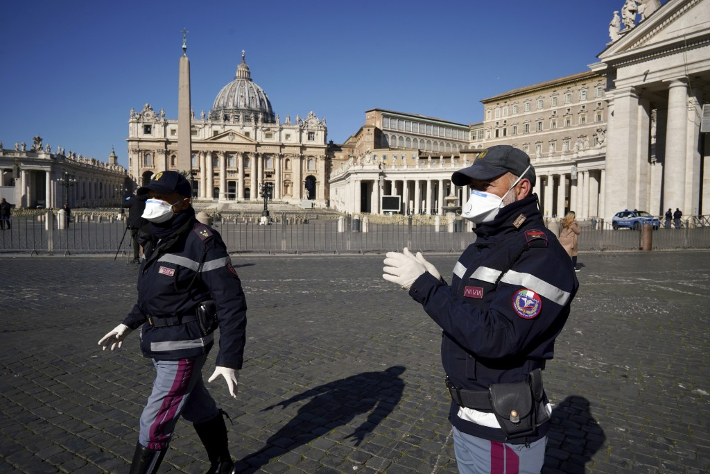 Police officers wearing masks patrol an empty St. Peter's Square at the Vatican, Wednesday, March 11, 2020. Pope Francis held his weekly general audie...