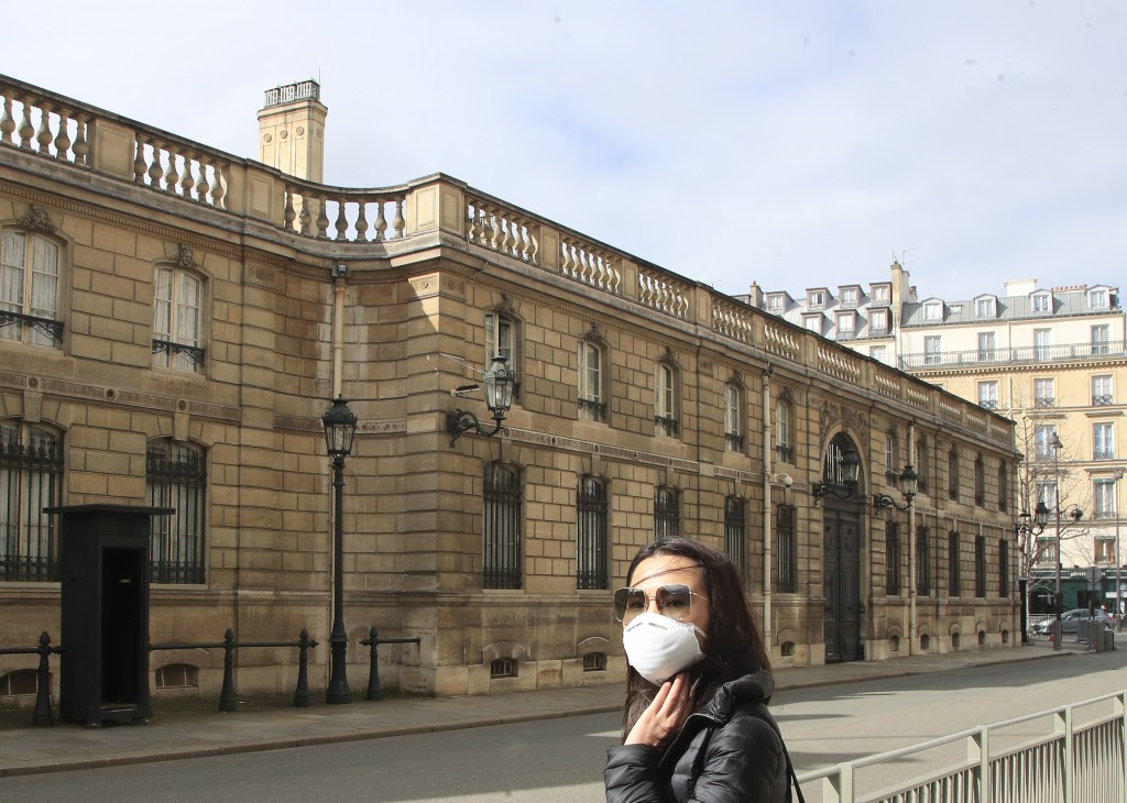 A woman wearing a mask as a precaution against the new coronavirus stands outside the Elysee Palace in Paris, Wednesday, March 11, 2020. France's gove...