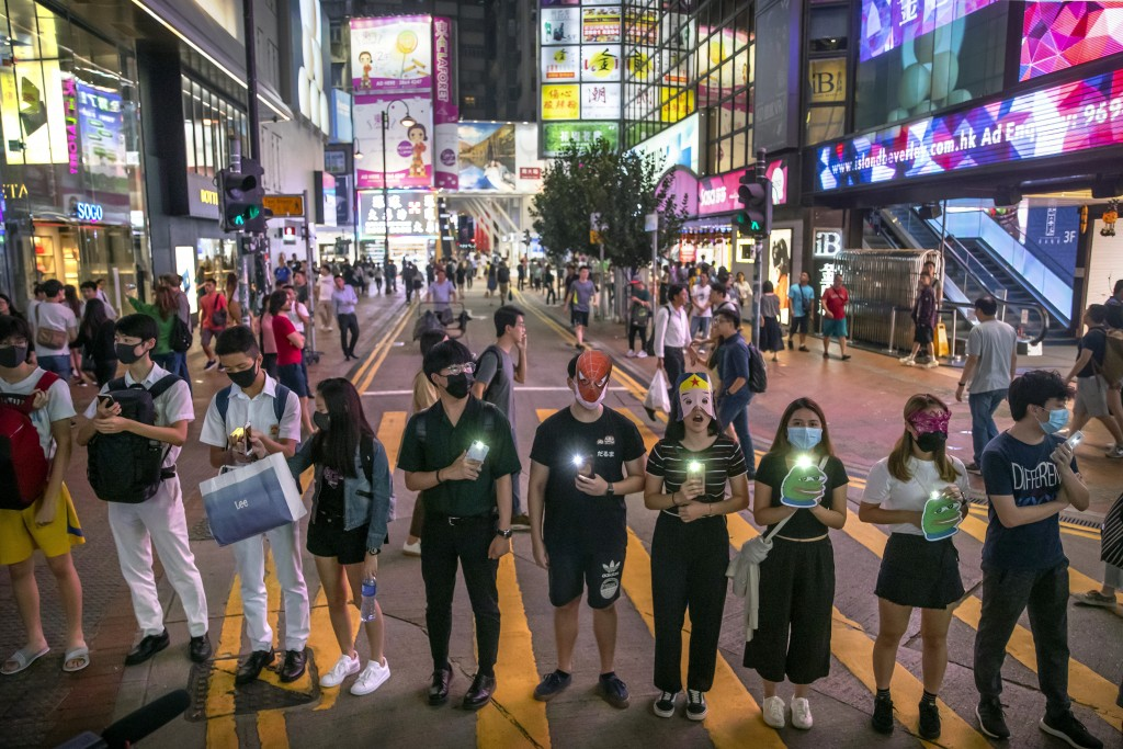 Protestors wearing masks stand along a commercial shopping street in Hong Kong last October