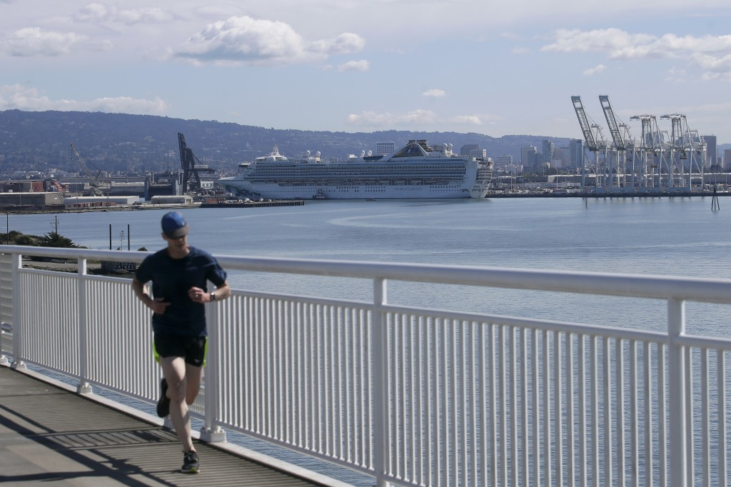 A man runs on the San Francisco-Oakland Bay Bridge pedestrian trail in front of the Grand Princess cruise ship, which carried multiple people who have...