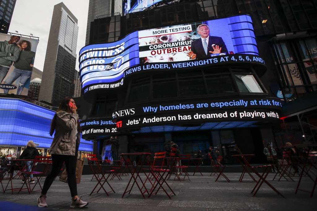 Pedestrians pass under a news ticker in Times Square, Wednesday, March 11, 2020, in New York, N.Y. The number of coronavirus cases in New York state j...
