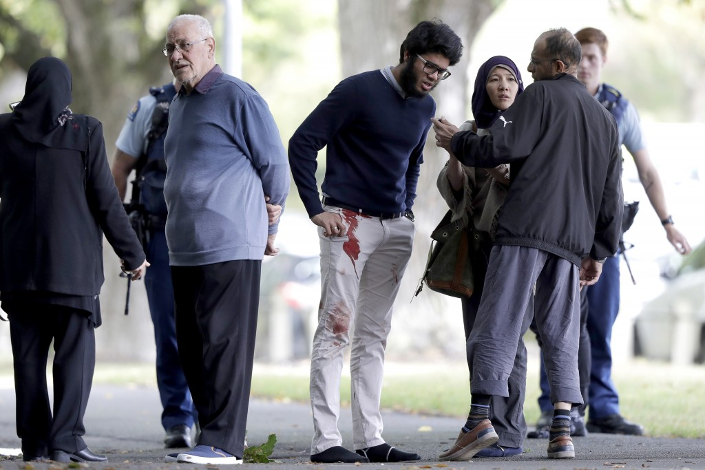 FILE - In this March 15, 2019, file photo, people stand across a road from the Al Noor mosque following a mass shooting in central Christchurch, New Z...
