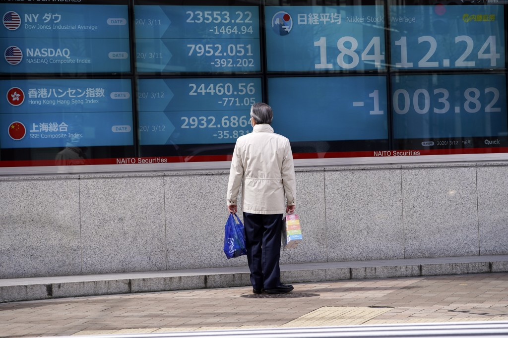 A man looks at an electronic stock board showing Japan's Nikkei 225 index at a securities firm in Tokyo Thursday, March 12, 2020. Asian shares plunged...