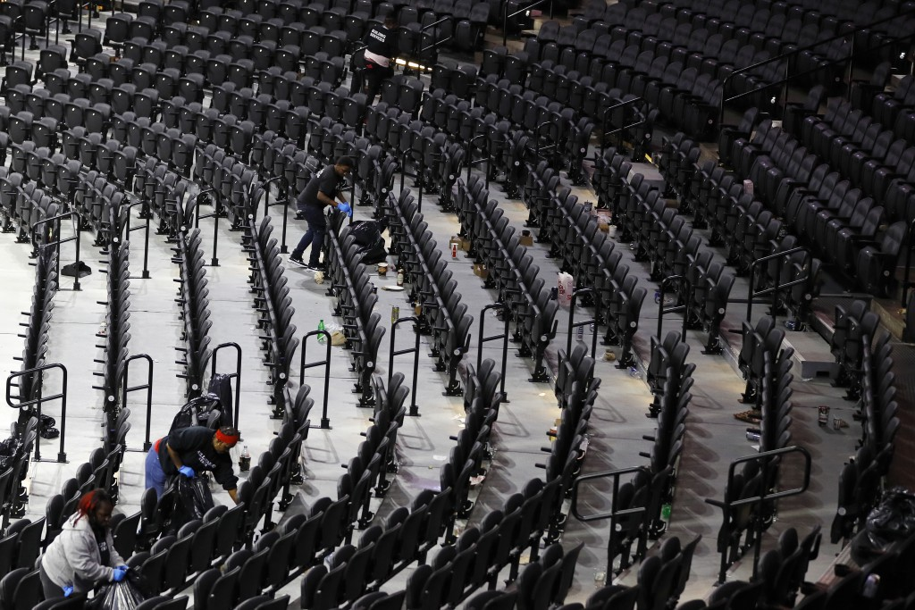 Workers clean the Wells Fargo Center after an NBA basketball game between the Philadelphia 76ers and the Detroit Pistons, Wednesday, March 11, 2020, i...