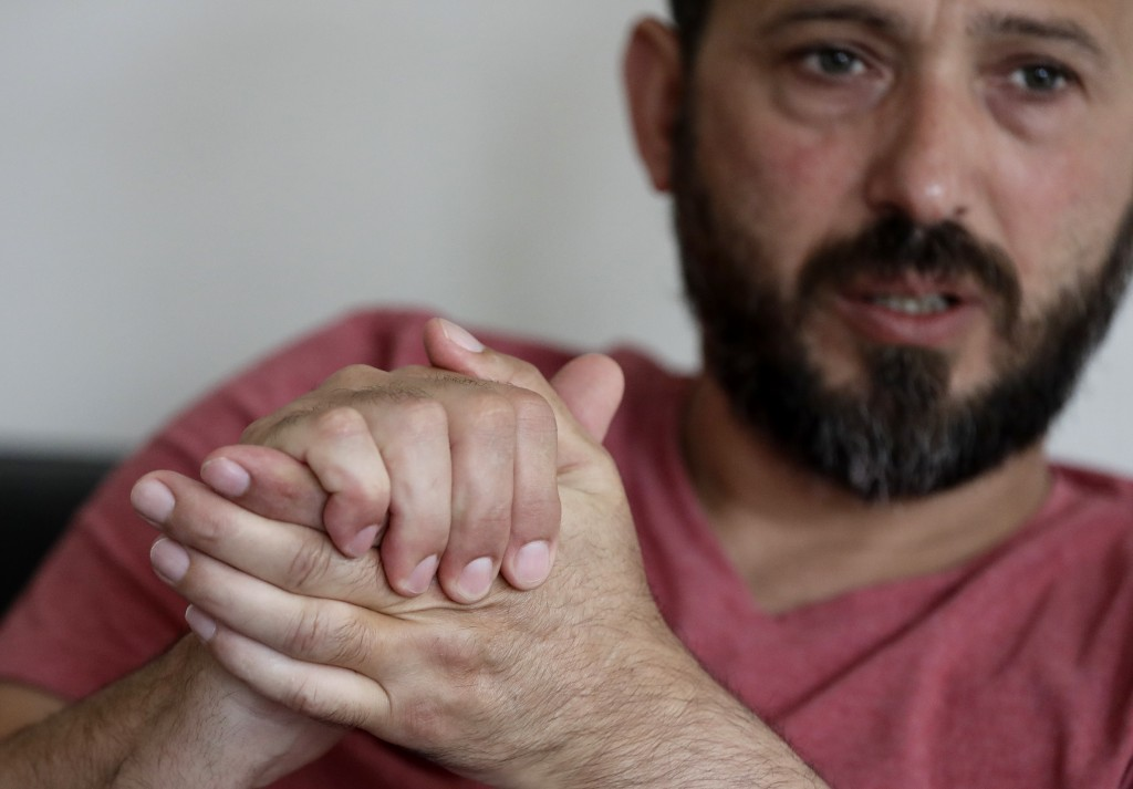 In this Tuesday, Feb. 25, 2020 photo, Al Noor mosque shooting survivor Temel Atacocugu gestures during an interview at his home in Christchurch, New Z...