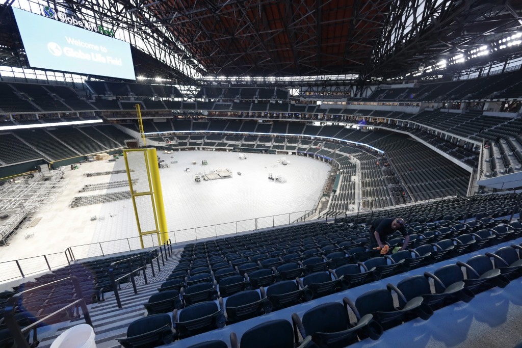 Worker Raul Camacho clean seats inside the newly constructed Globe Life Field in Arlington Texas, Wednesday, March 11, 2020. The Texas Rangers are sch...