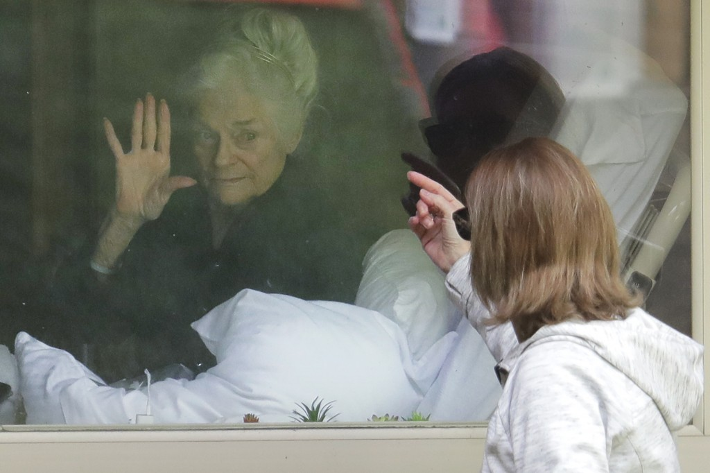 Judie Shape, left, who has tested positive for the coronavirus, waves to her daughter, Lori Spencer, right, Wednesday, March 11, 2020, as they visit o...