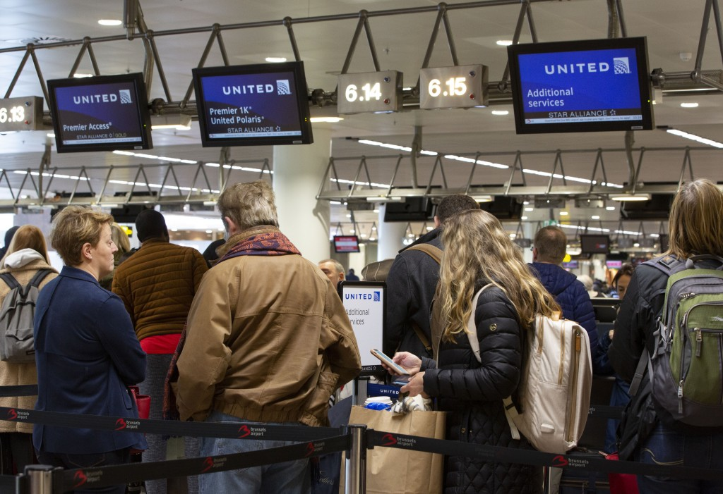 People wait to check in to a flight to Chicago at the United Airlines counter in the main terminal of Brussels International Airport in Brussels Thur