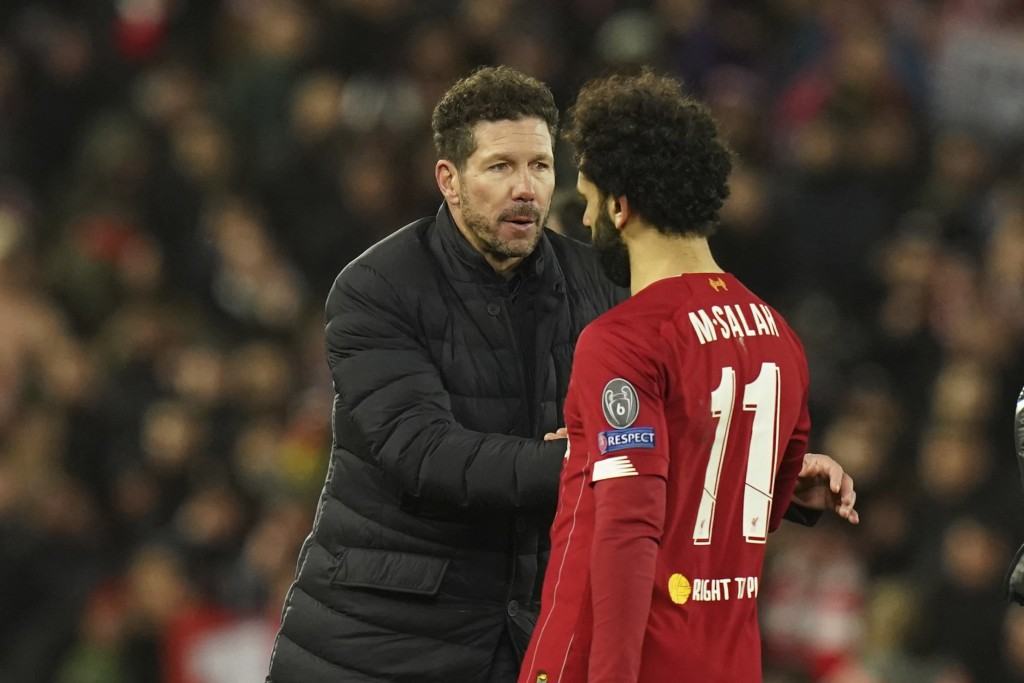 Atletico Madrid's head coach Diego Simone, left, greets Liverpool's Mohamed Salah at the end of the second leg, round of 16, Champions League soccer m...