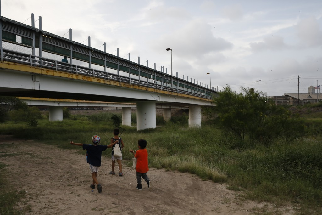 FILE - In this June 26, 2019 file photo, migrant children walk with their families along the Rio Grande, as pedestrian commuters use the Puerta Mexico...