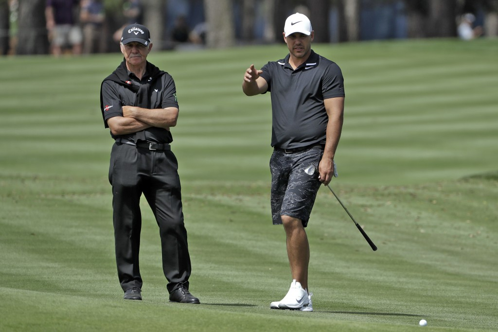 Brooks Koepka, right, gestures as he talks to his short game coach Peter Cowen during a practice round for The Players Championship golf tournament We...