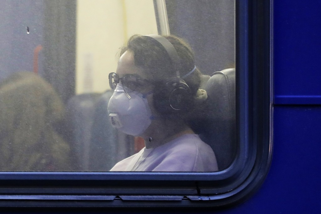 In this March 6, 2020 photo, a woman wears a mask as she rides a bus in downtown Seattle during an evening commute. Expressing alarm both about mounti...