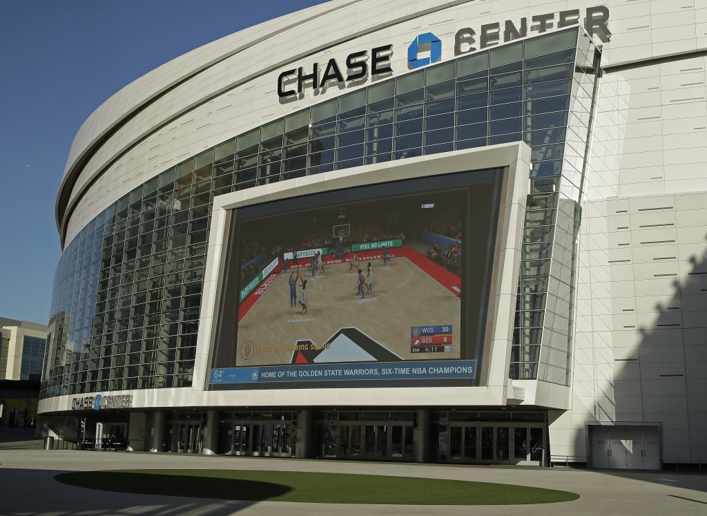 The Chase Center, home of NBA basketball's Golden State Warriors, show a pre-recorded video of a basketball game on a large screen at the entrance to ...