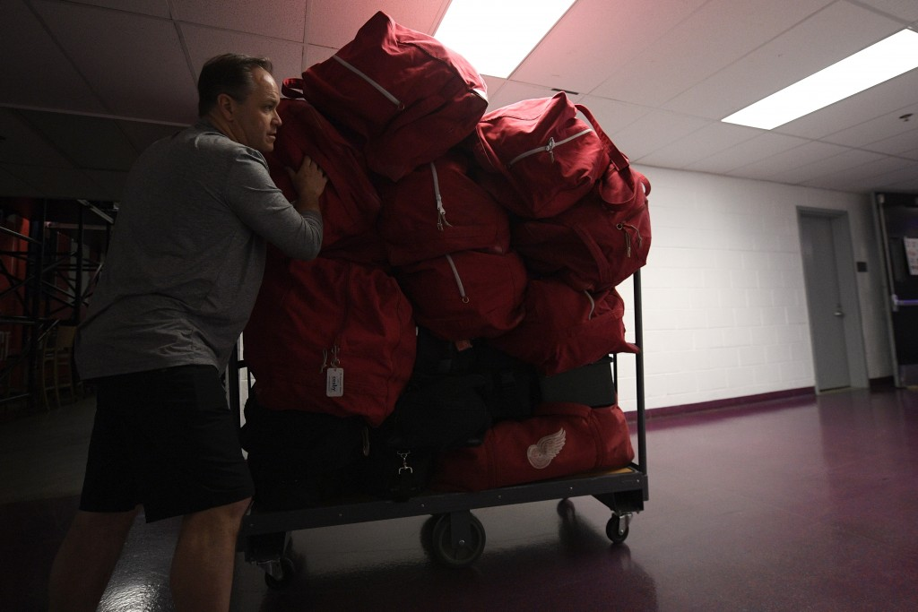Paul Boyer, head equipment manager of The Detroit Red Wings NHL hockey team, wheels out equipment bags in the hallway of Capital One Arena, Thursday, ...