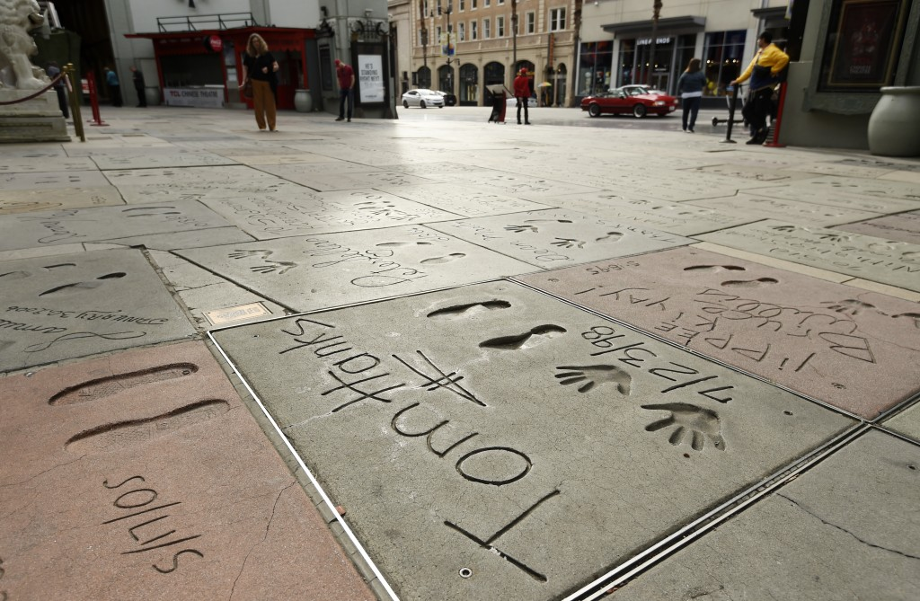 The cement inscription of actor Tom Hanks sits in the nearly empty forecourt of the TCL Chinese Theatre, Thursday, March 12, 2020, in the Hollywood se...