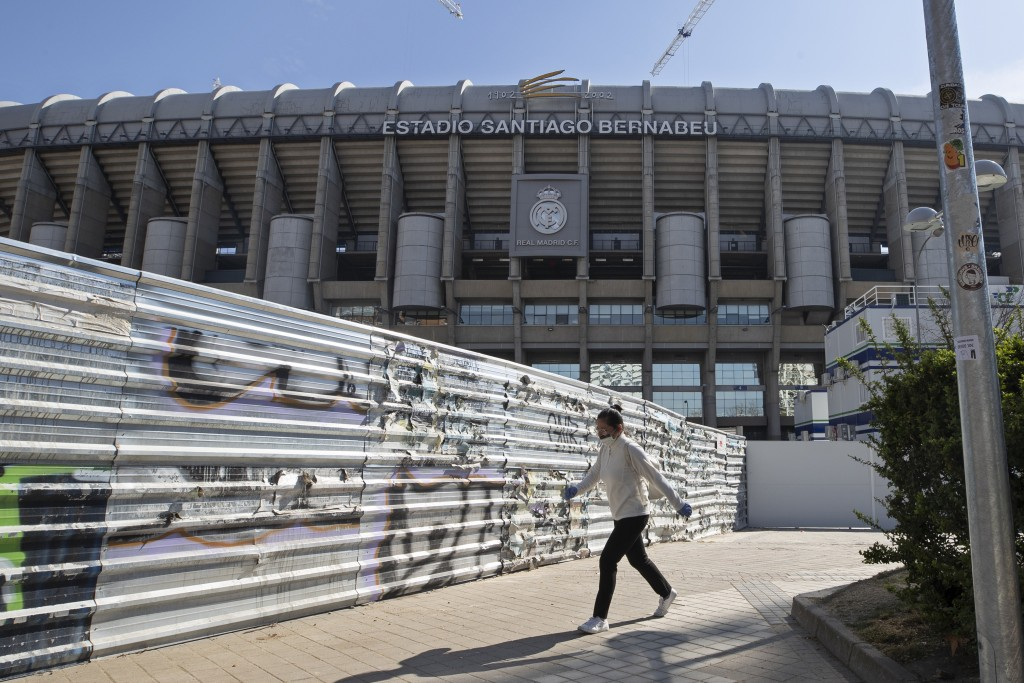A woman wearing a protective mask walks past Real Madrid's Santiago Bernabeu stadium in Madrid, Spain, Friday, March 13, 2020. Real Madrid have said i...