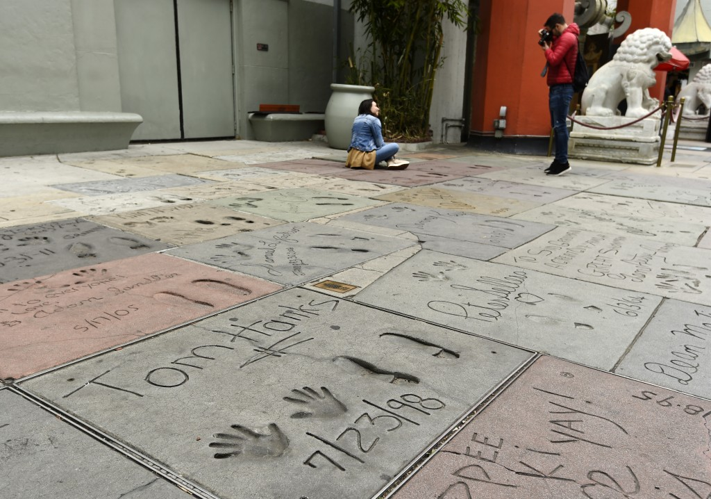 Visitors take pictures near the cement inscription of actor Tom Hanks in the forecourt of the TCL Chinese Theatre, Thursday, March 12, 2020, in the Ho...