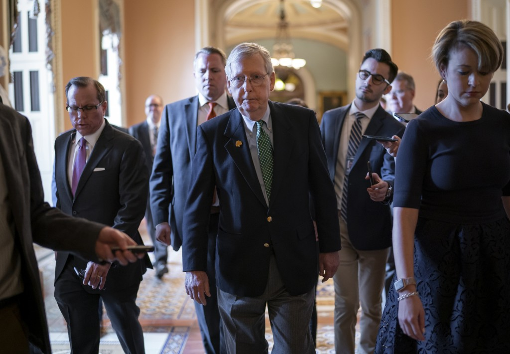 Senate Majority Leader Mitch McConnell, R-Ky., walks through a crowd of reporters after announcing he has canceled the Senate recess next week, at the...
