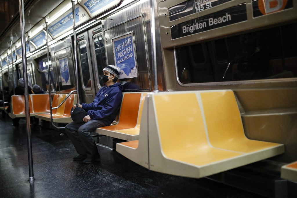A commuter wears a face mask while riding the a nearly empty subway car into Brooklyn, Thursday, March 12, 2020, in New York. New York City Mayor Bill...