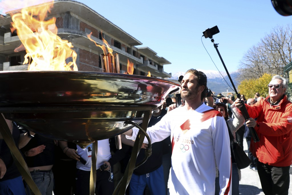 US actor Gerard Butler lights an altar as a torchbearer during the Olympic torch relay of the 2020 Tokyo Olympic Games in the southern Greek town of S...