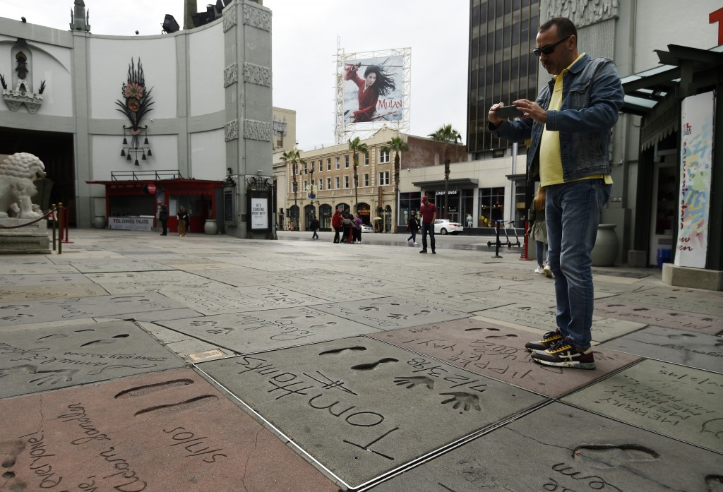 A man takes a picture of the hand and footprints of actor Tom Hanks in the forecourt of the TCL Chinese Theatre, Thursday, March 12, 2020, in the Holl...