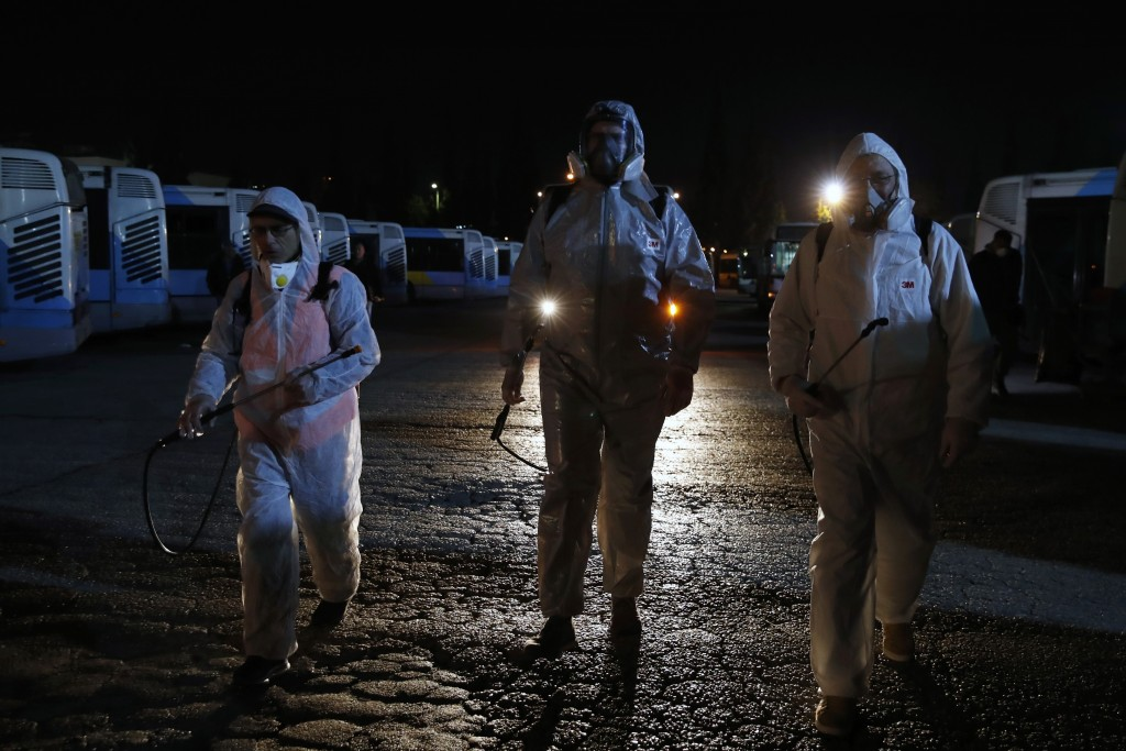 Workers wearing protective suits walk at a bus depot before they spray disinfectant inside the vehicles in Athens, Saturday, March 14, 2020. Greece ha...