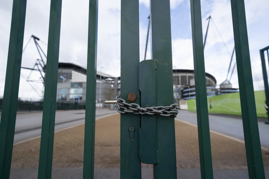 A locked gate is seen by the Etihad Stadium where Manchester City was due to play Burnley in an English Premier League soccer match Saturday March 14,...