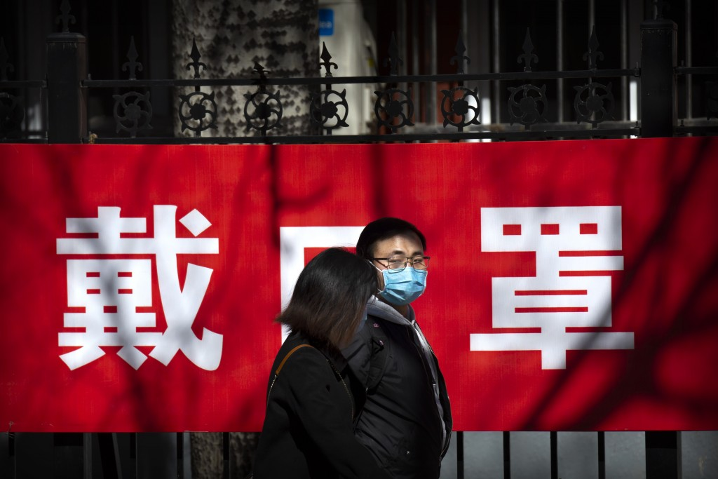 """People walk past a propaganda banner reading """"wear a face mask"""" in Beijing, Saturday, March 14, 2020. The United States declared a state of emergency ..."""