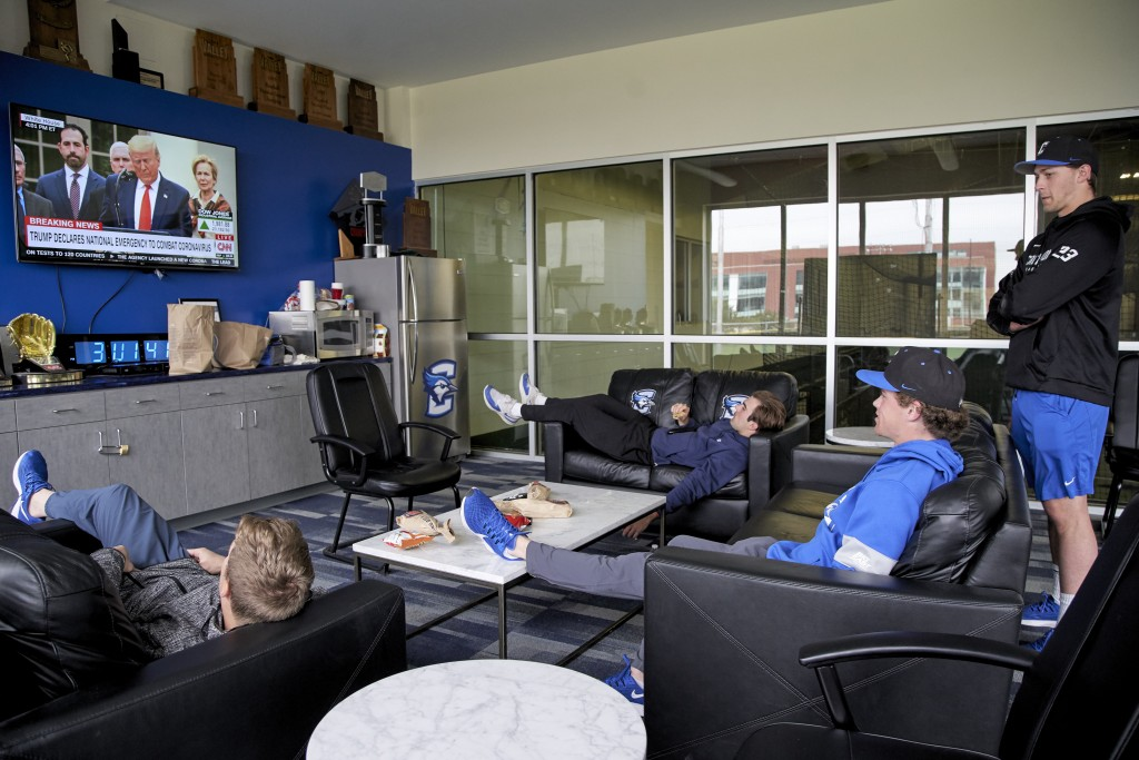 In this March 13, 2020 photo, Creighton NCAA college baseball pitchers Ben Dotzler, right, and Tommy Steier, second right, watch President Trump decla...