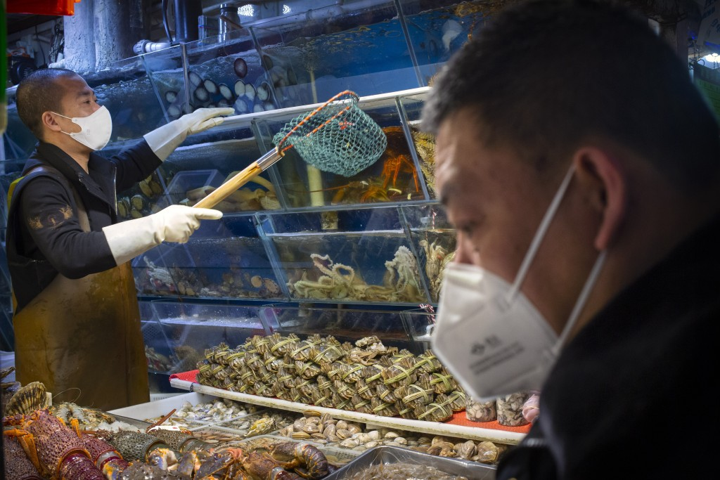 A customer wears a face mask as he shops for seafood at a market in Beijing, Saturday, March 14, 2020. The United States declared a state of emergency...