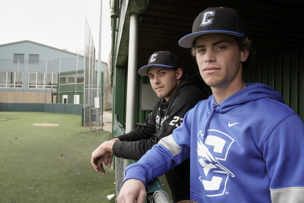 In this March 13, 2020 photo, Creighton NCAA college baseball pitchers Ben Dotzler and Tommy Steier, right, stand in the third base dugout in Omaha, N...