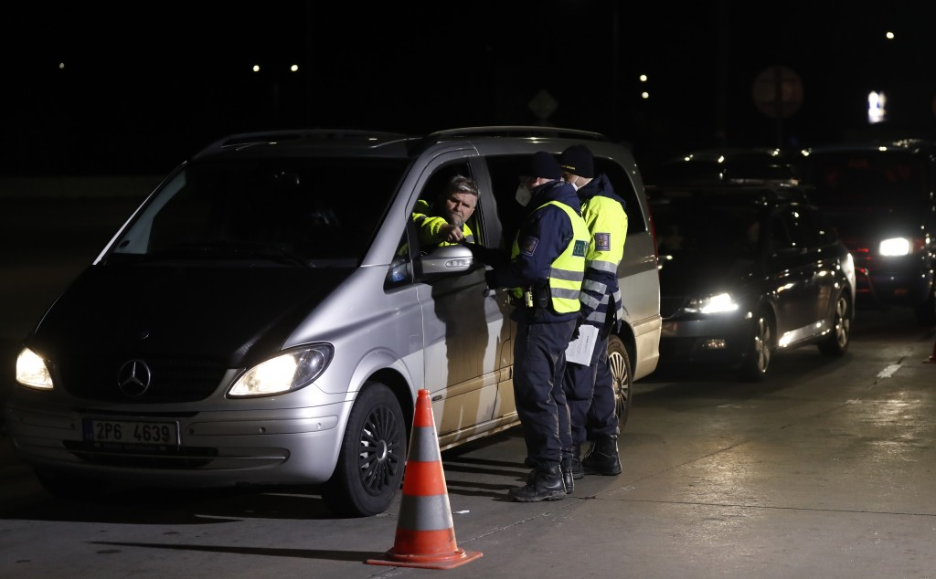 Customs and police officers check the documents of a traveler at the border crossing with Germany in Rozvadov, Czech Republic, Friday, March 13, 2020....