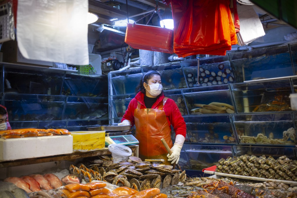 An employee wears a face mask as she works at a seafood stall at a market in Beijing, Saturday, March 14, 2020. The United States declared a state of ...