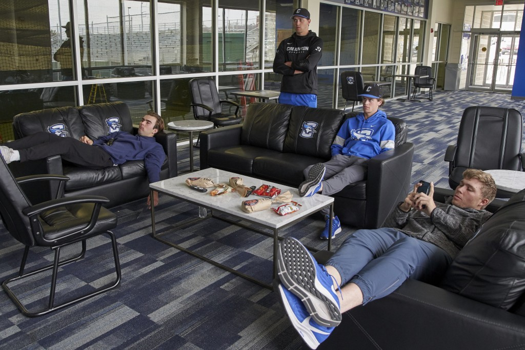 In this March 13, 2020 photo, Creighton NCAA college baseball pitchers Ben Dotzler, top center, and Tommy Steier, second right, watch President Trump ...