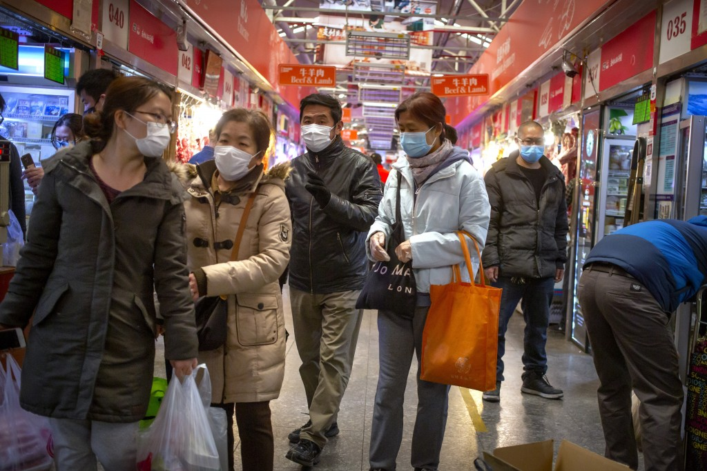 People wear face masks as they shop at a market in Beijing, Saturday, March 14, 2020. The United States declared a state of emergency Friday as many E...