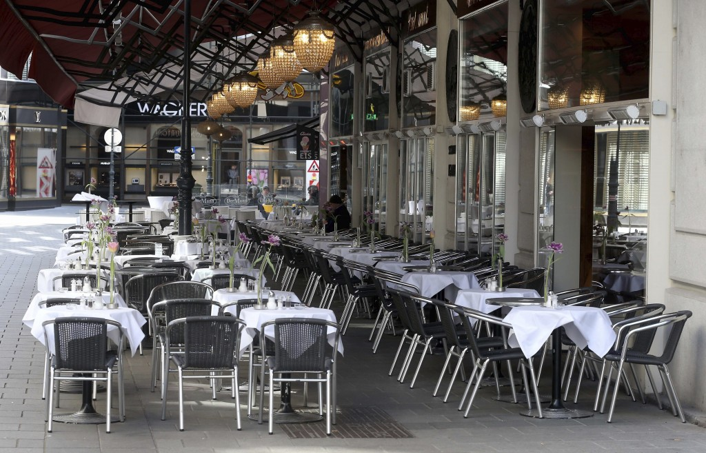 Guests are sitting in an outdoor restaurant at the pedestrian zone in Vienna, Austria, Sunday, March 15, 2020. The austrian government restricts freed...