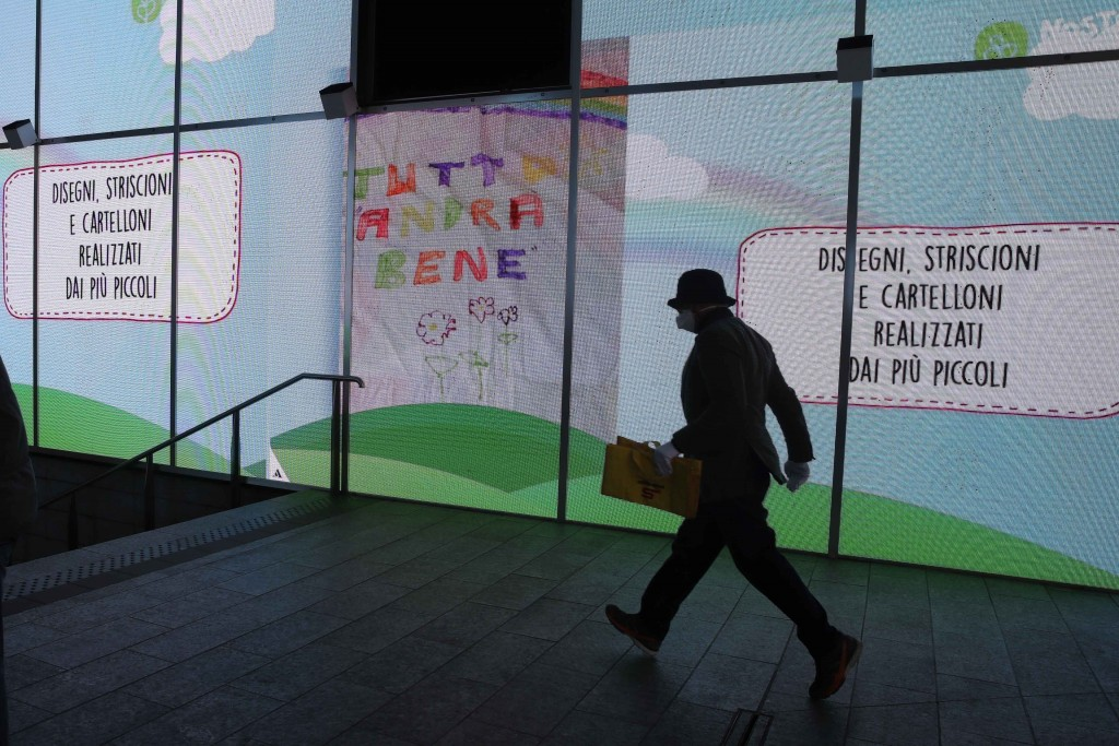 """In this photo taken on Saturday, March 14, 2020 a man walks past a billboard, center, reading in Italian """"Everything will be alright"""", in Milan, Italy..."""