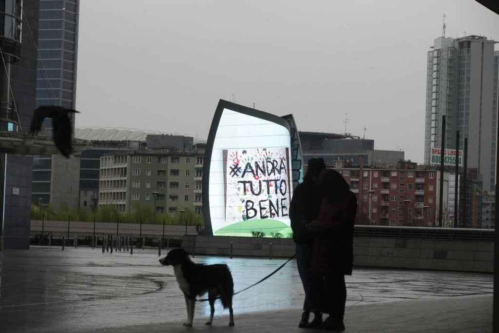 """In this photo taken on Saturday, March 14, 2020 a couple and their dog stand by a billboard reading in Italian """"Everything will be alright"""", in Milan,..."""