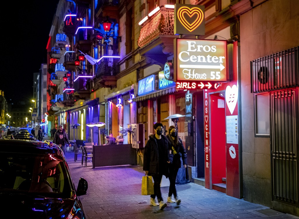 A couple wearing face masks walk through the red light district in Frankfurt, Germany, Saturday, March 14, 2020. For most people, the new coronavirus ...