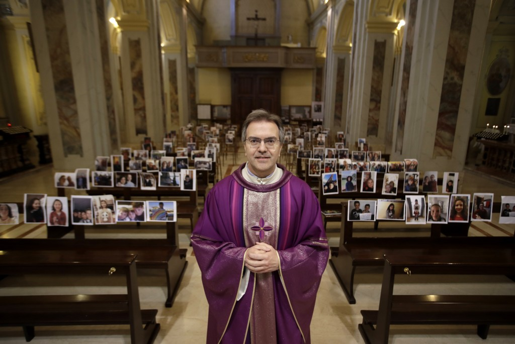 Robbiano Church parson, Don Giuseppe Corbari, poses in front of selfies he was sent by parishioners as Masses for the faithful have been suspended fol...