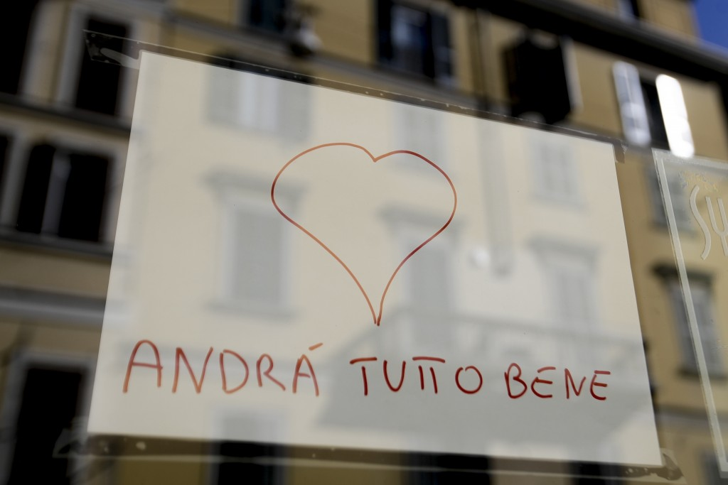 """In this photo taken on Wednesday, March 11, 2020, a note reading in Italian """"Everything will be alright"""" hangs on the window of a shop in Milan, Italy..."""