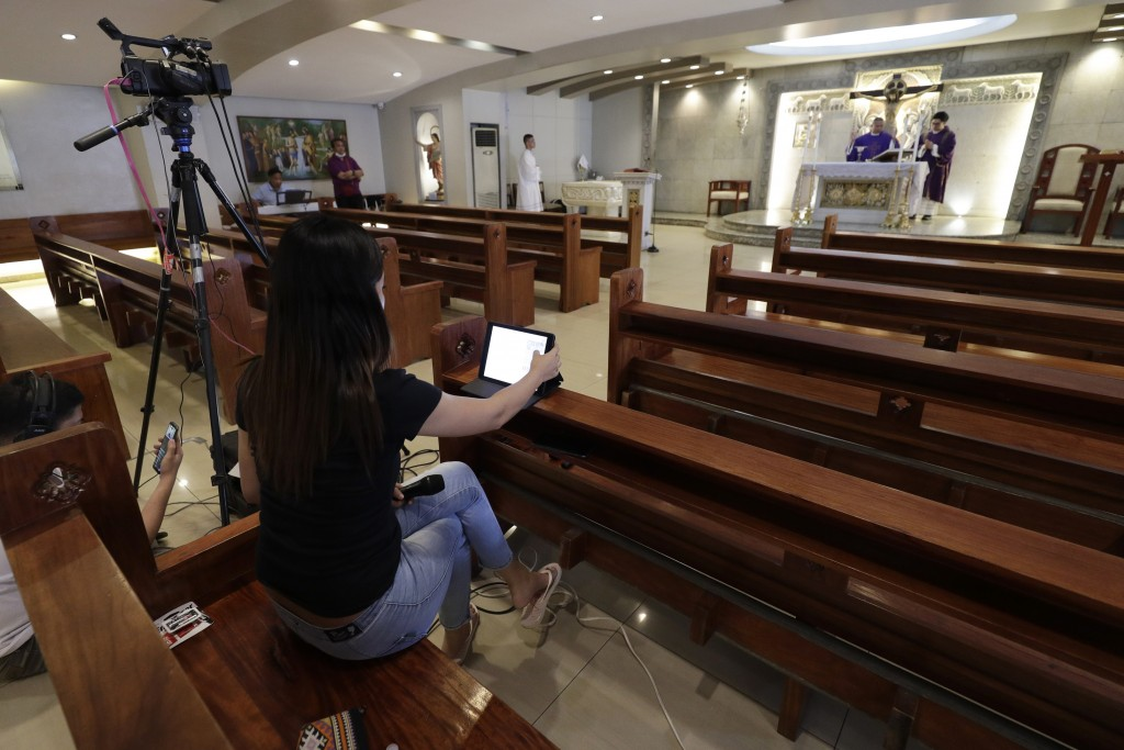 Catholic priest Rymond Ratilla presides over a mass that is live video streamed on their Facebook page at an empty Chapel of the Nativity of the Bless...
