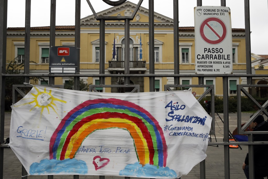"""In this photo taken on Saturday, March 14, 2020, a banner reading """"Everything will be alright"""" hangs on the main gate of the Spallanzani Hospital for ..."""
