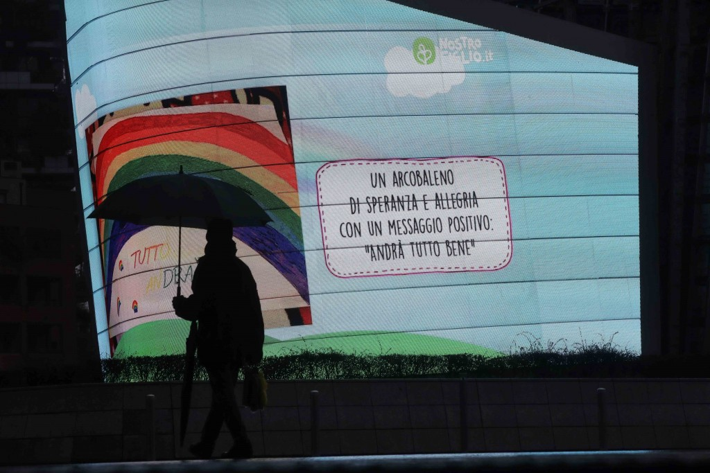 """In this photo taken on Saturday, March 14, 2020 a man walks past a billboard reading in Italian """"A Rainbow of hope and cheerfulness with a positive me..."""