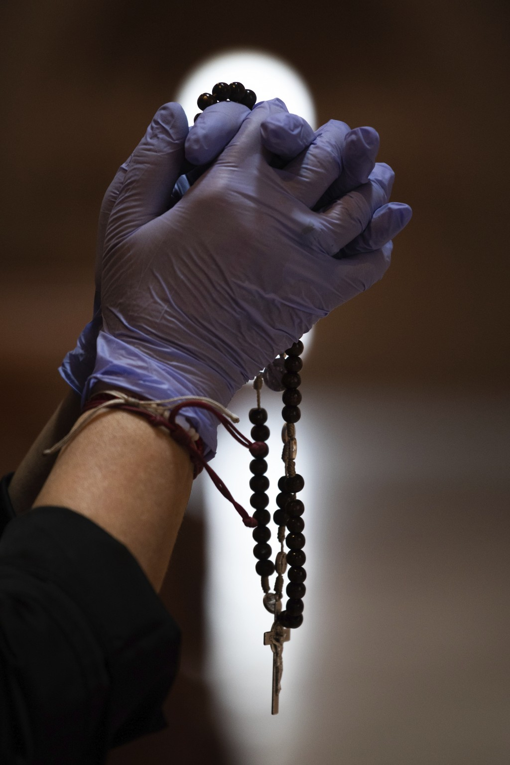 A Catholic worshipper using protective gloves prays with a rosary beads at the Santa Maria de Cana parish in Pozuelo de Alarcon, outskirts Madrid, Spa...