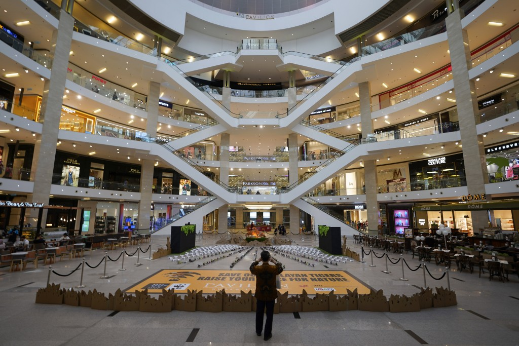 A shopper takes a picture at an empty shopping mall in Kuala Lumpur, Malaysia, Sunday, March 15, 2020. For most people, the new coronavirus causes onl...