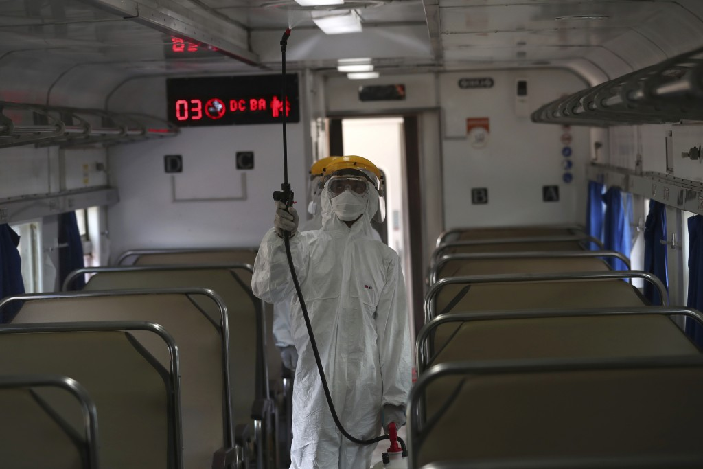 An employee in protective gears sprays disinfectant in the wake of coronavirus outbreak inside a train at the Senen train station in Jakarta Indonesia...