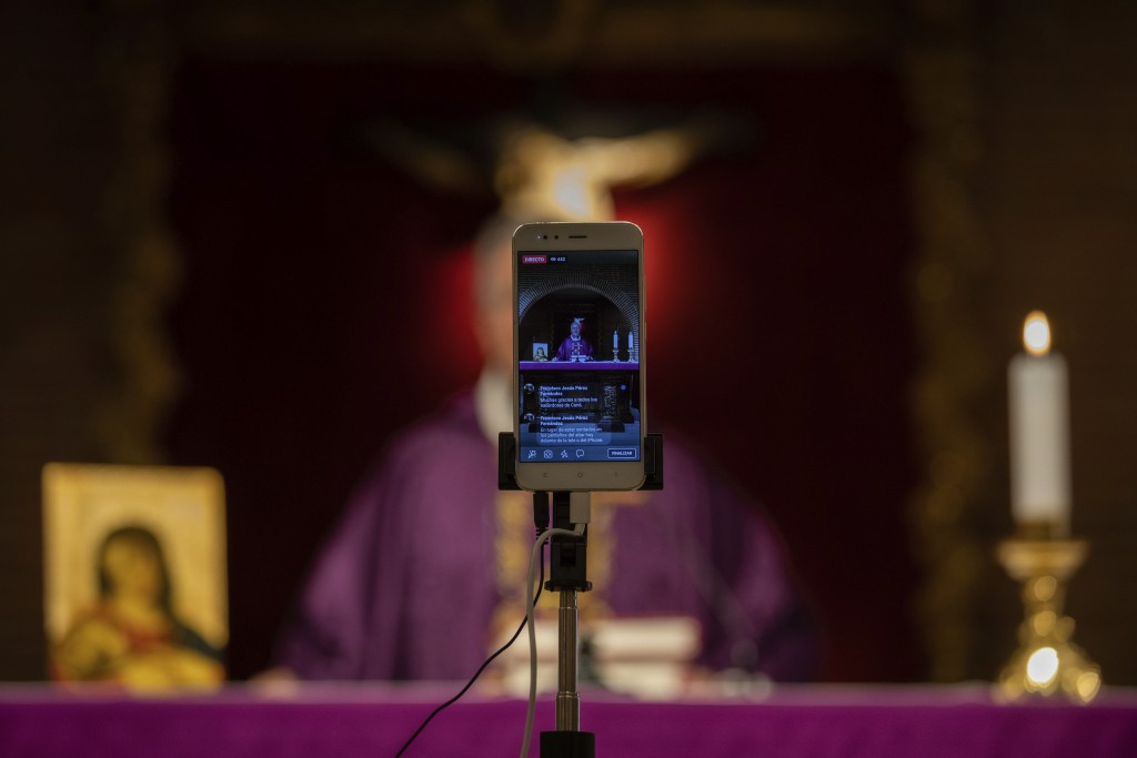 Catholic priest Catholic priest Jesus Higueras from the Santa Maria de Cana parish is seen on a smartphone during a live video streamed mass in Pozuel...
