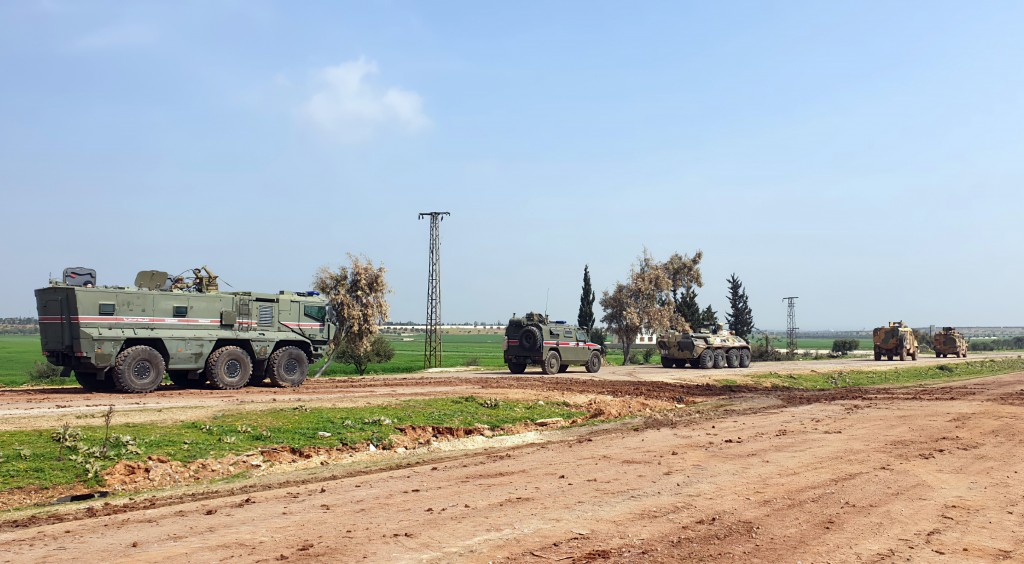 In this photo provided by the Turkish Defense Ministry, Turkish and Russian troops patrol on the M4 highway, which runs east-west through Idlib provin...